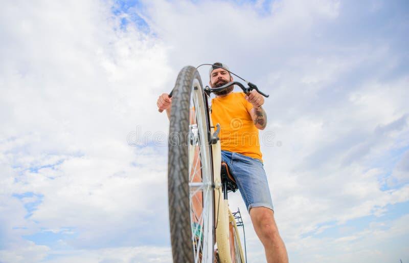 自行车转动购物指南 人有胡子的行家乘坐自行车底视图天空背景 自行车机械工忠告 保留 库存图片