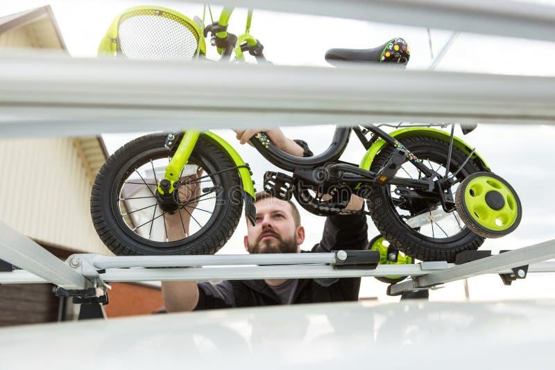 自行车运输-一个人在汽车的屋顶紧固并且安装小孩子的自行车在特别登上为 库存图片