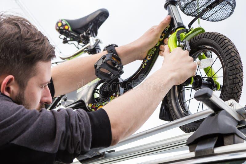 自行车运输-一个人在汽车的屋顶紧固并且安装小孩子的自行车在特别登上为 免版税库存图片