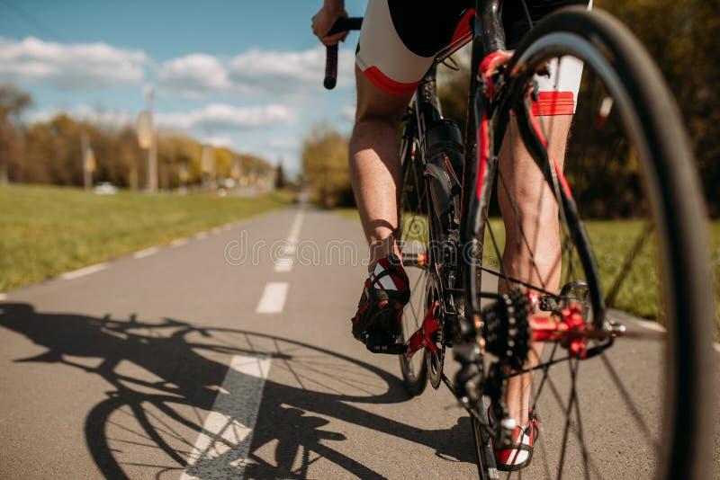 自行车道路的,从后轮的看法骑自行车者 免版税库存照片