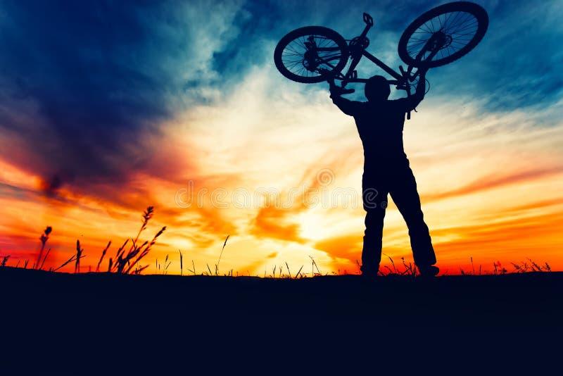 自行车骑士上升的自行车和庆祝比赛的第一个地方剪影  库存照片