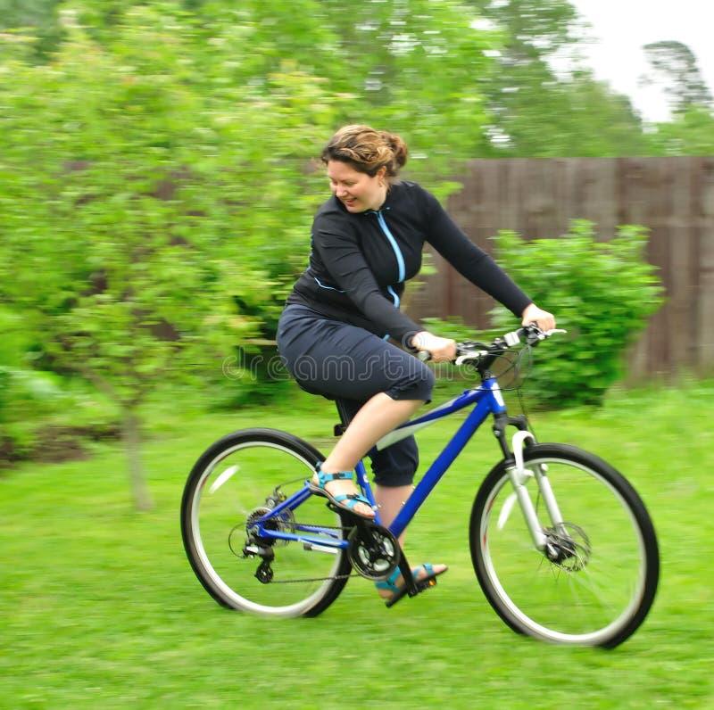 自行车骑马微笑的妇女 库存照片