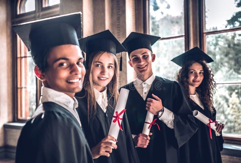 自豪地是毕业生 微笑小组微笑的大学毕业生一起站立在大学和看照相机 免版税图库摄影