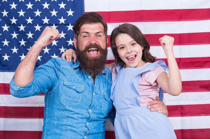 自豪地是美国人 庆祝独立日的愉快的美国家庭 有胡子的人和小孩有优胜者的 图库摄影