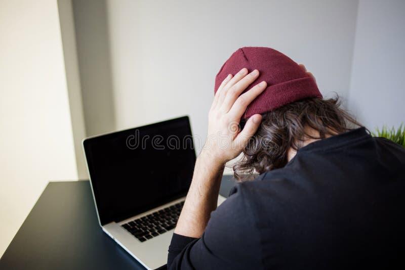 臭虫和错误在发展 一位年轻程序员在工作场所有问题在工作 免版税库存照片
