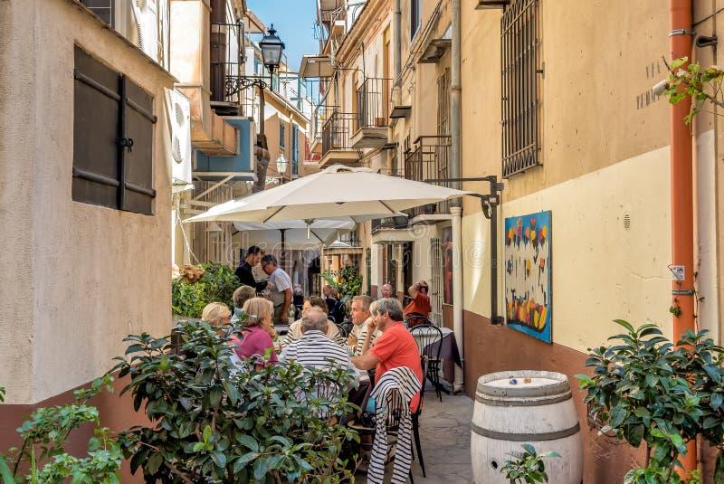 至多坐在一条狭窄的街道的人们酒吧在蒙雷阿莱的历史的中心 图库摄影