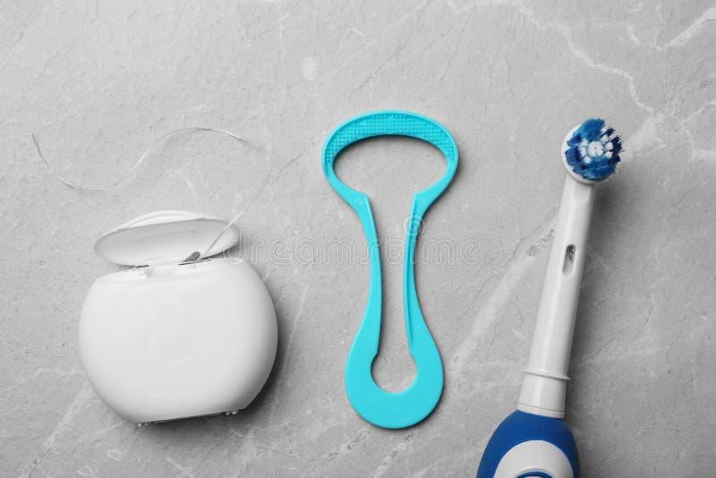 舌头擦净剂、牙线和电牙刷在灰色背景 免版税图库摄影