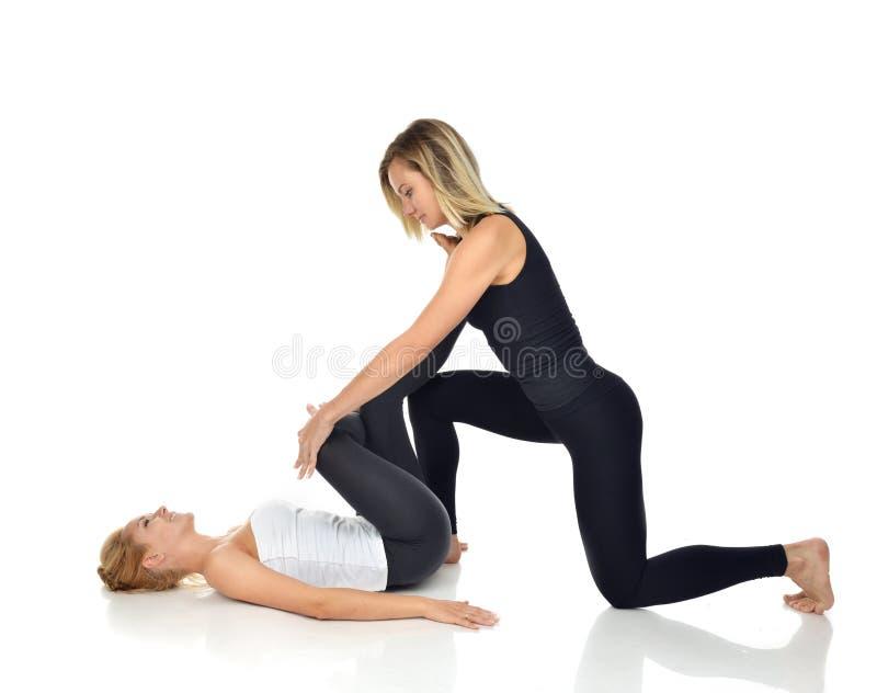 舒展一名年轻体育妇女的医生生理治疗师 免版税库存照片