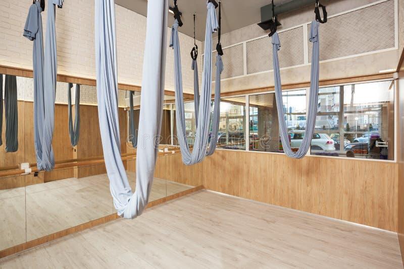舒展与空中瑜伽丝绸吊床和镜子的演播室内部 免版税库存照片