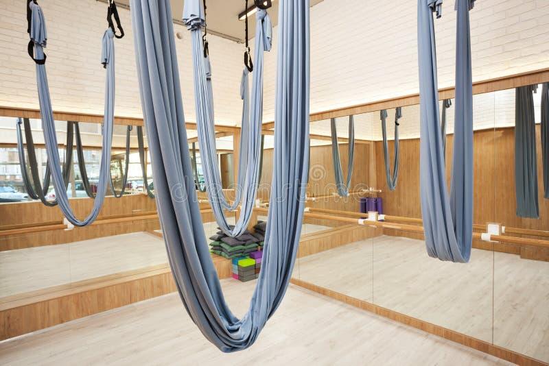 舒展与空中瑜伽丝绸吊床和镜子的演播室内部 免版税库存图片