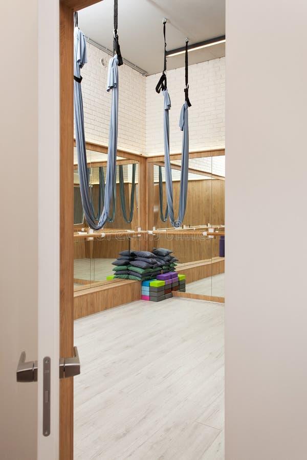 舒展与空中瑜伽丝绸吊床和镜子的演播室内部 库存图片