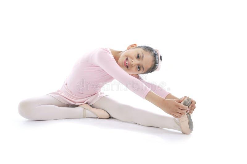 舒展佩带的桃红色芭蕾芭蕾舞短裙的年轻逗人喜爱的芭蕾舞女演员女孩 免版税图库摄影