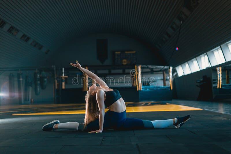 舒展做垂直的分裂的体操运动员女孩,麻线 做核心锻炼的可爱的年轻女人侧视图 免版税库存照片