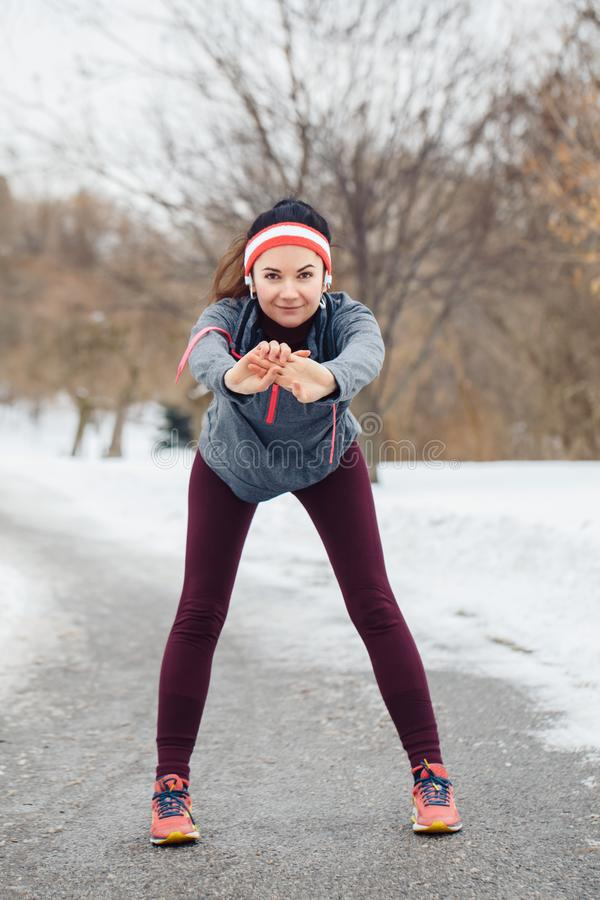 舒展和做准备为跑步的少妇外面在冬天公园 免版税图库摄影