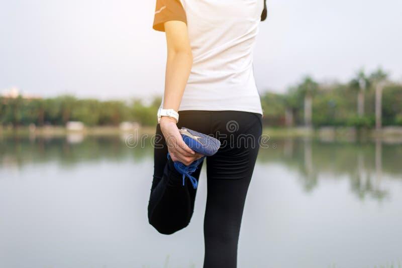 舒展和做准备在跑或锻炼惯例前的妇女在室外 免版税库存图片
