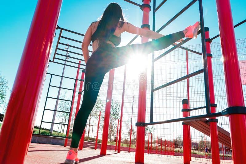 舒展和行使户外在城市环境里的健身妇女 免版税库存图片