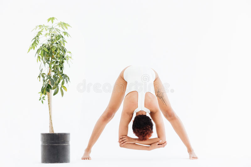 舒展和行使瑜伽的灵活的非裔美国人的少妇 免版税库存照片