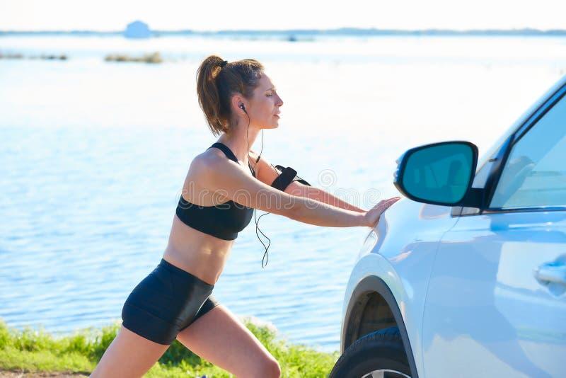 舒展在一辆汽车的赛跑者妇女在湖 库存图片