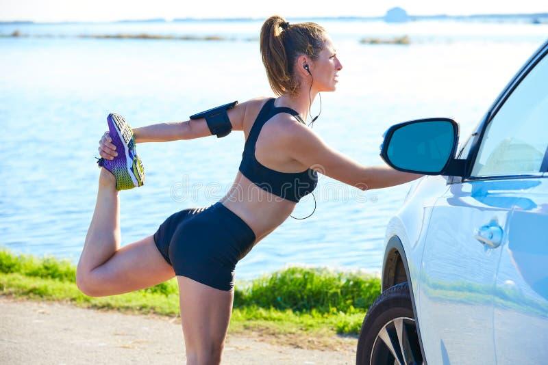 舒展在一辆汽车的赛跑者妇女在湖 免版税库存照片
