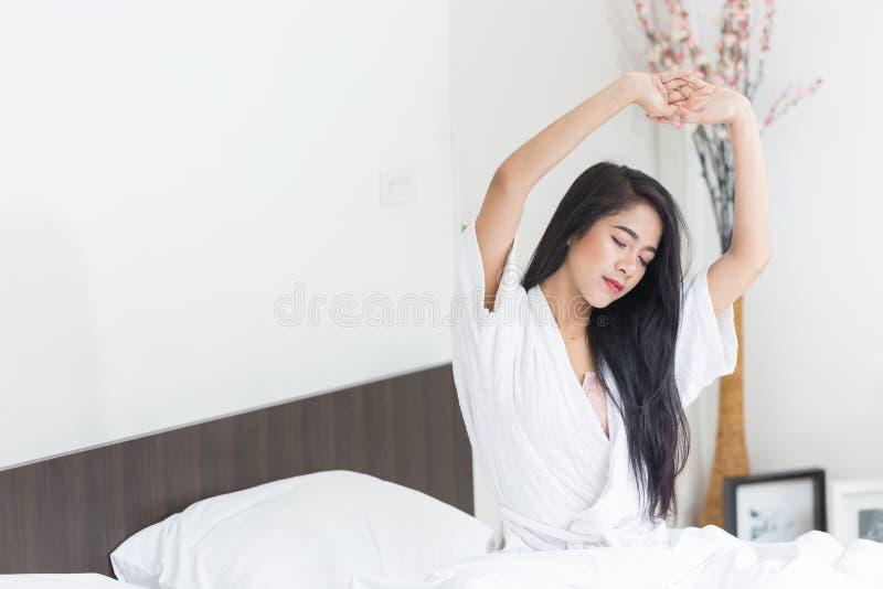 舒展在与她的胳膊的床上的亚裔妇女上升了 免版税库存图片