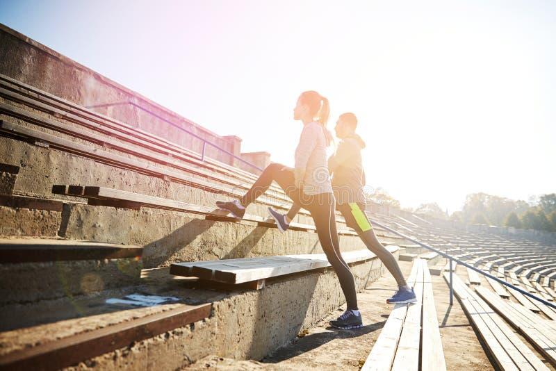 舒展在体育场立场的夫妇腿  免版税库存照片