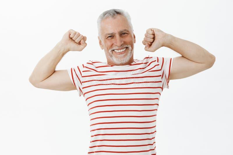舒展在做得好以后的老人感觉领抚恤金者佩带的镶边T恤杉愉快和被加强的居住的活跃生活  库存图片