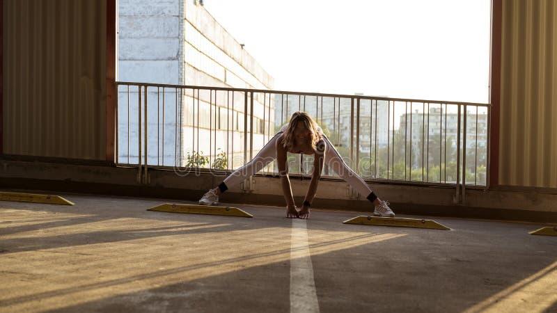 舒展在停车处的健康有动机的sportwoman肌肉 库存照片