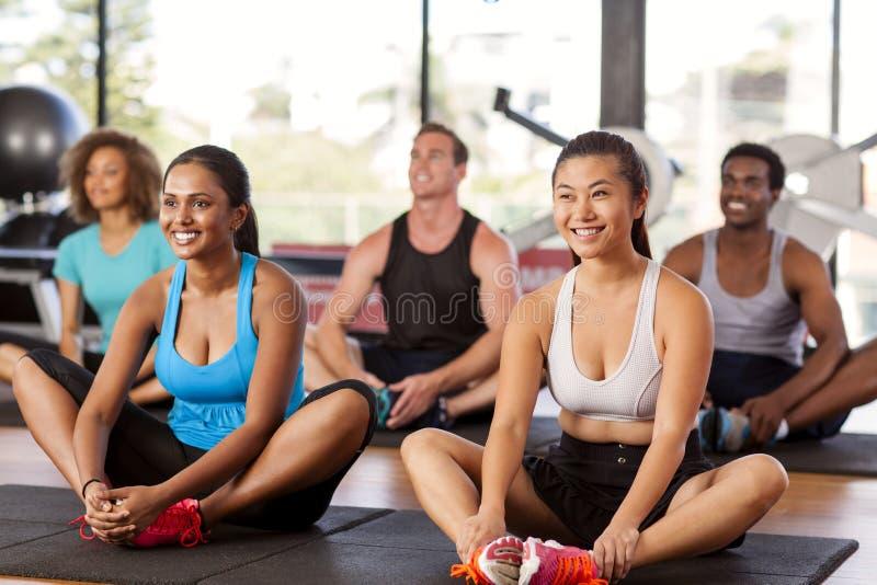舒展在健身房的不同种族的小组 库存照片