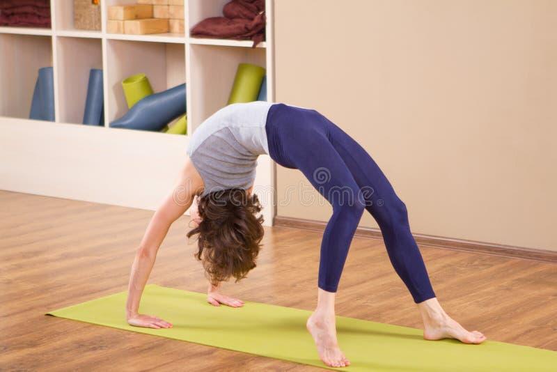 舒展在健身房的年轻运动的妇女 免版税库存照片