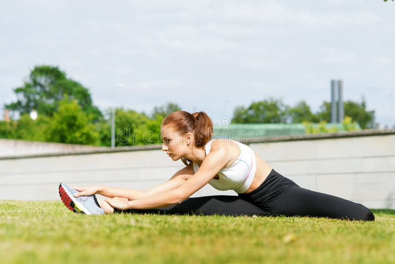 舒展在公园的年轻人、适合和运动的妇女 健身,体育,都市和健康生活方式概念 免版税图库摄影