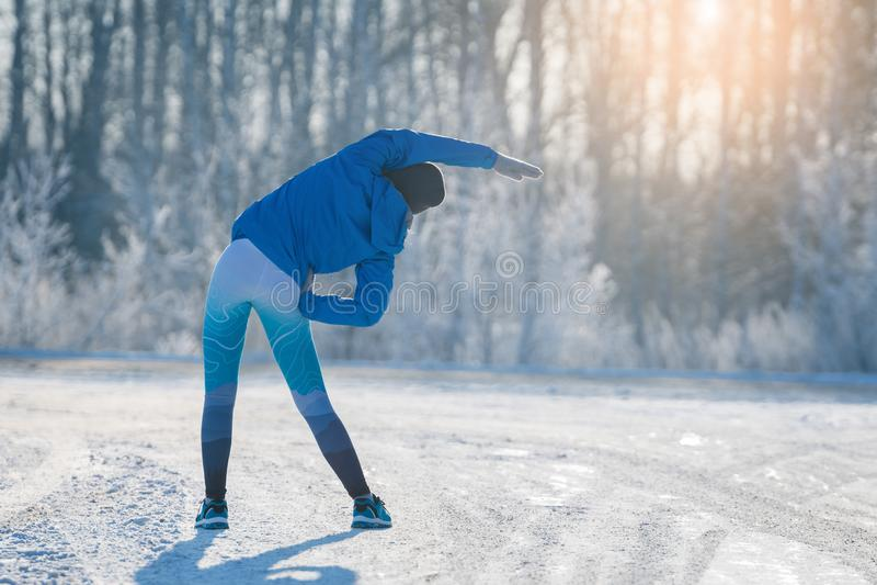 舒展在冬天公园的赛跑者 健康生活方式 库存图片