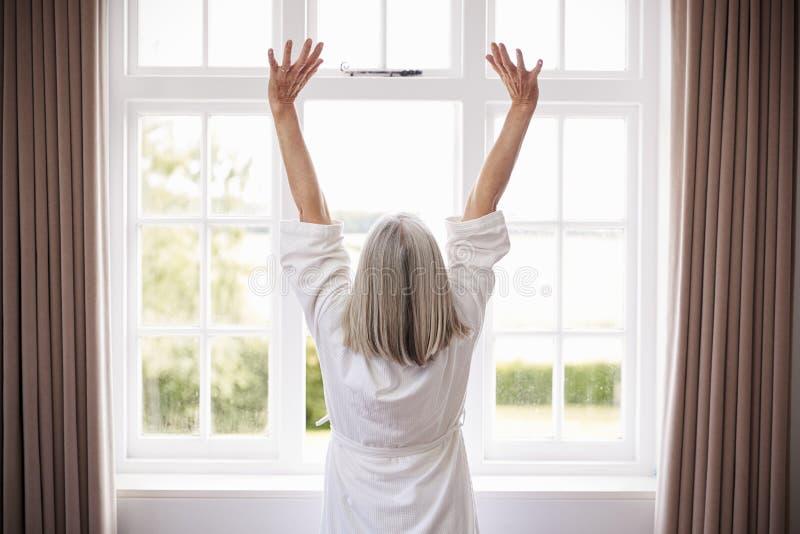 舒展在卧室窗口前面的资深妇女背面图 库存图片