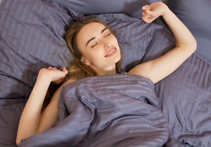 舒展在叫醒的美丽的年轻女人一会儿以后在舒适卧室床上,微笑的休息的女孩感觉刷新了坐白色 库存图片