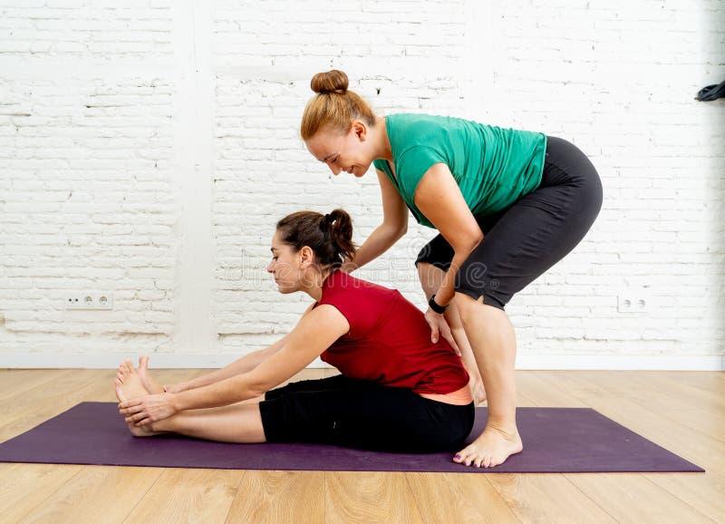 舒展在坚强和健康妇女的瑜伽教练帮助的年轻女人实践的瑜伽姿势 免版税库存照片