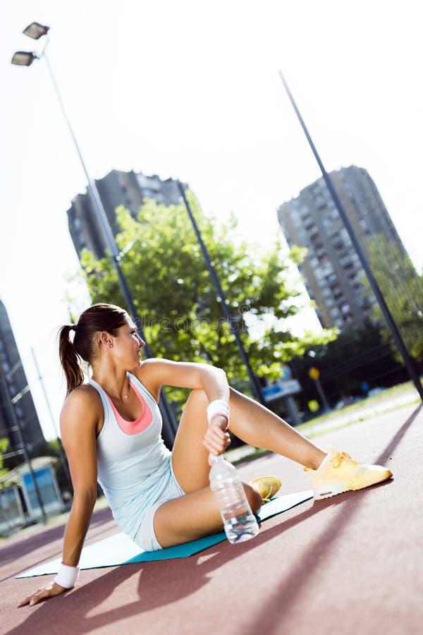 舒展在夏天的美丽的年轻运动妇女 免版税库存图片