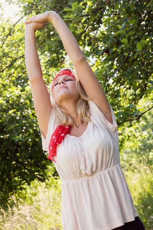 舒展在夏天风景的少妇 免版税库存照片