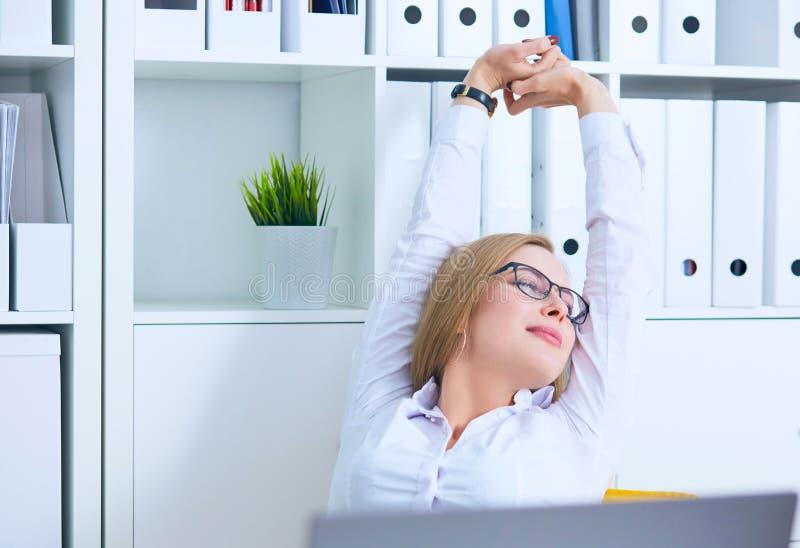 舒展在她的工作场所和微笑在办公室的玻璃的可爱,少妇 图库摄影