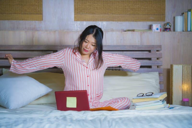 舒展在床上的年轻美丽的疲乏和困亚裔韩国学生女孩在后学习为学院检查的长时间以后与 免版税图库摄影