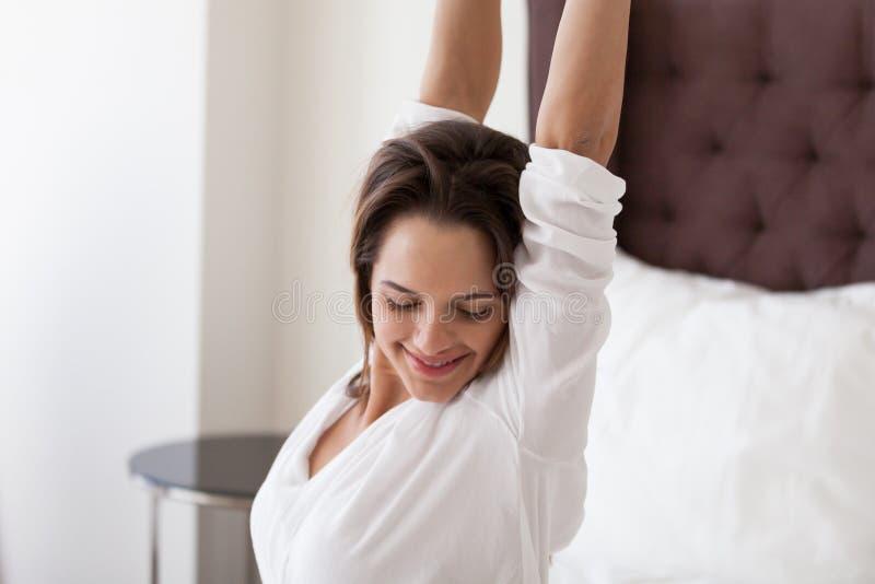 舒展在床上的微笑的妇女享用叫醒愉快的概念 免版税库存照片