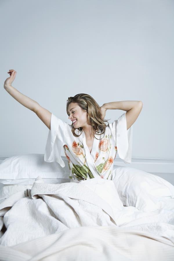 舒展在床上的愉快的妇女 免版税库存照片