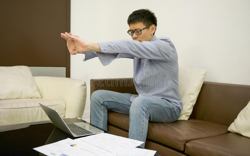舒展在有文件的膝上型计算机前面的亚洲商人 免版税图库摄影