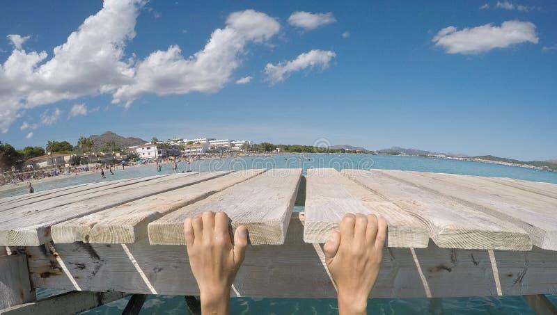 舒展在海滩的一个木码头的女孩的手 免版税库存图片
