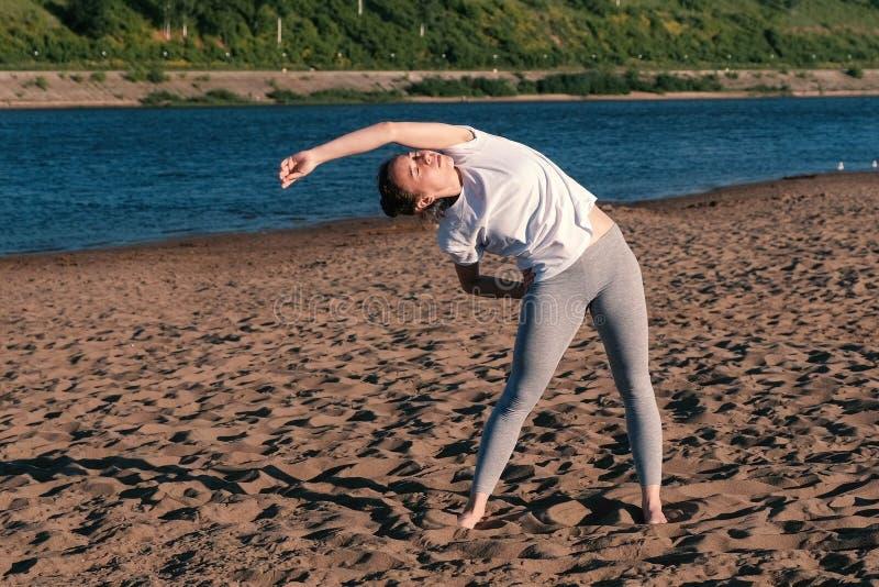 舒展在海滩的妇女瑜伽由河在城市 美丽的景色 对边的掀动 库存图片