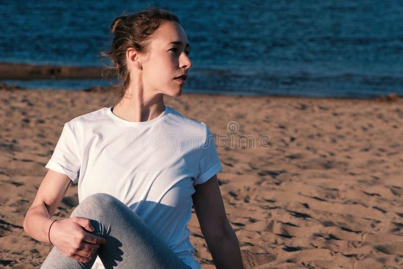 舒展在海滩的妇女瑜伽由河在城市 美丽的景色 免版税库存照片
