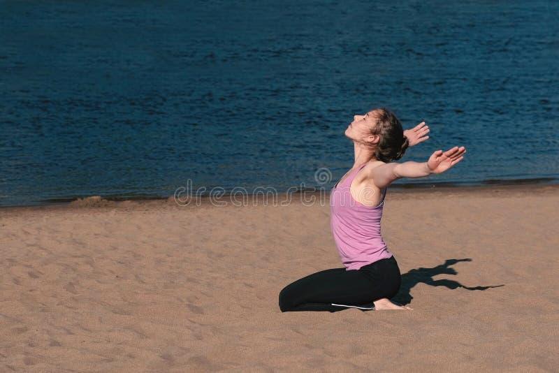 舒展在海滩的妇女瑜伽由河在城市 美好的城市视图 呼吸的锻炼 免版税图库摄影