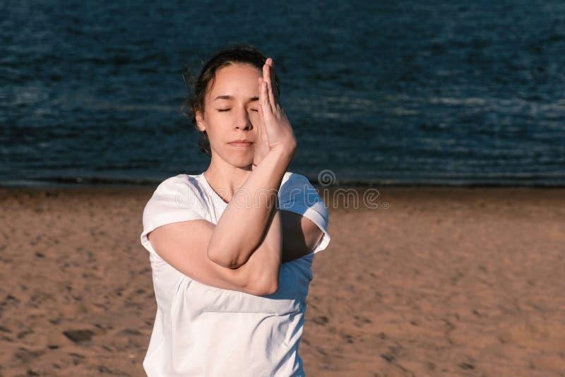 舒展在海滩的妇女瑜伽由河在城市 美好的城市视图 Namaste姿势 免版税图库摄影