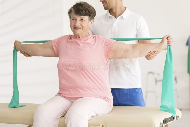 舒展在物理疗法期间的年长妇女 库存图片