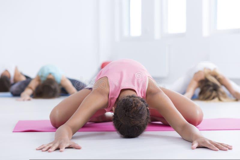 舒展在瑜伽席子的人们 免版税图库摄影