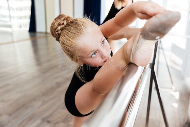 舒展在舞蹈课的小舞蹈家腿 免版税图库摄影