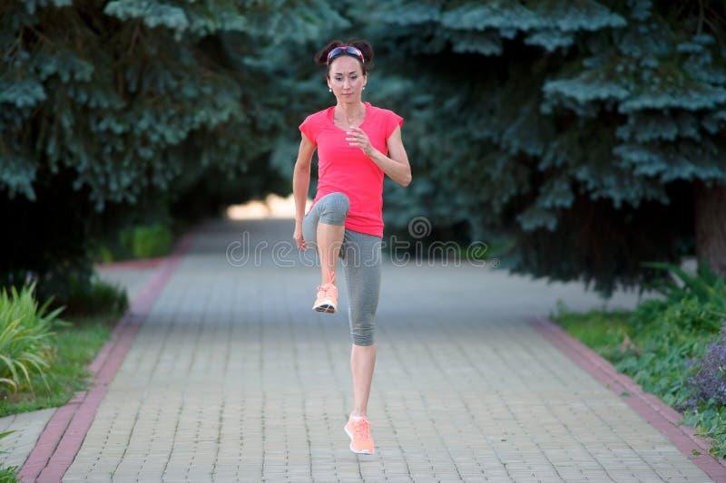 舒展在跑前的嬉戏妇女 嬉戏女孩exercisi 免版税库存图片